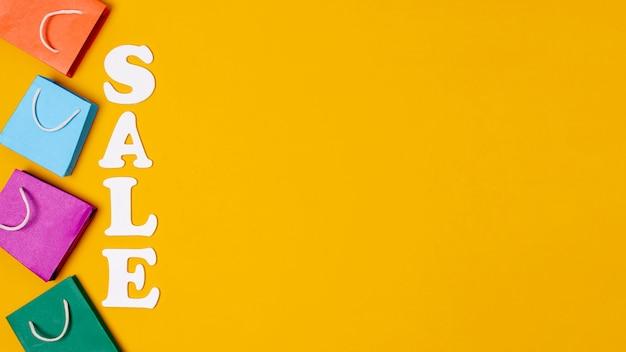 Verkoop met papieren zakken concept op oranje achtergrond en kopie ruimte Gratis Foto