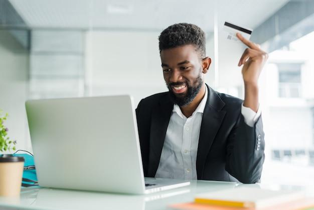 Verkoop via internetbankieren. succesvolle afrikaanse zakenmanzitting bij laptop en creditcard in hand houdt tot zakenman die orden doen door internet Gratis Foto