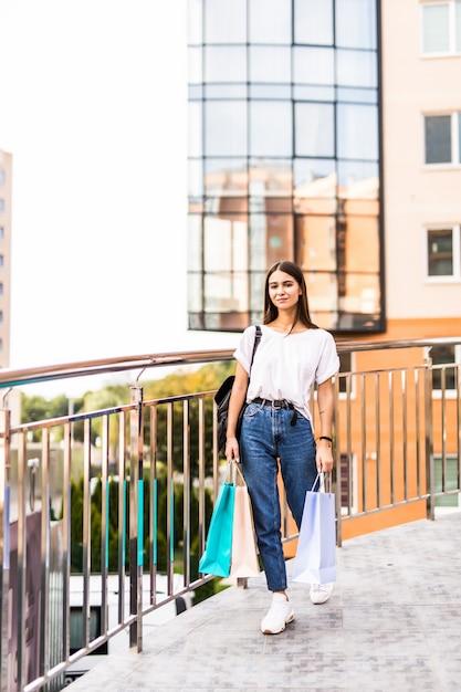 Verkoop, winkelen, toerisme en gelukkige mensen concept - mooie vrouw met boodschappentassen in het centrum Gratis Foto