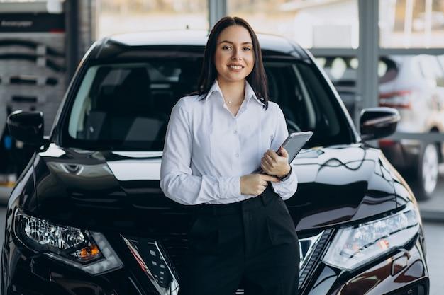 Verkoopster in autotoonzaal die auto's verkoopt Gratis Foto