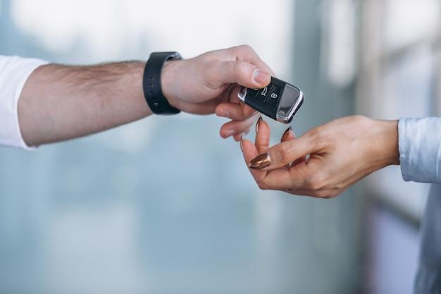 Verkoper en vrouw die een auto in een autotoonzaal zoeken Gratis Foto