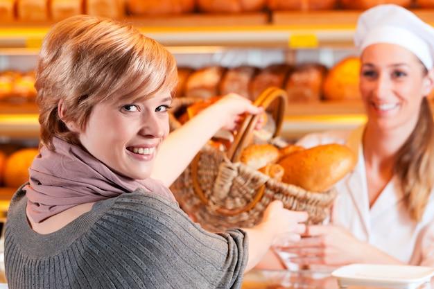 Verkoper met vrouwelijke klant in bakkerij Premium Foto