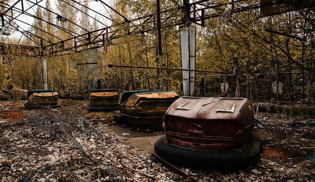 Verlaten pretpark met roestige auto's in pripyat-stad bij de uitsluitingsstreek van tsjernobyl. Premium Foto