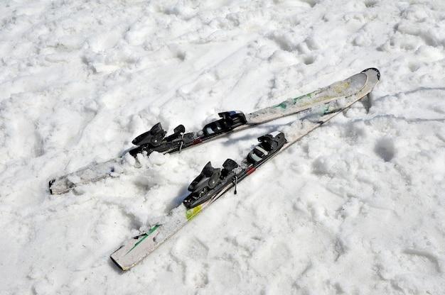 Verlaten ski's in de sneeuw. bovenaanzicht. skiseizoen einde concept. Premium Foto