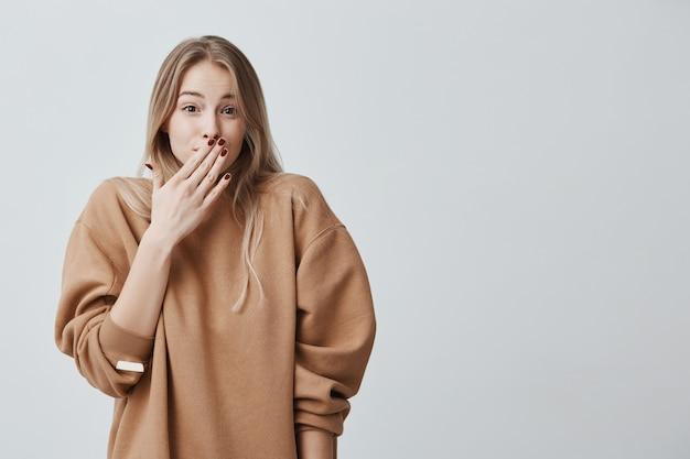 Verlegen jonge vrouw. de vrouw die van het close-upportret met blond haar beschaamd of verlegen kijken, die in vol ongeloof, geschokt door nieuws zijn, verbergend geïsoleerd gezicht achter hand ,. Gratis Foto