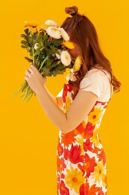 Verlegen meisje met bloemboeket Gratis Foto