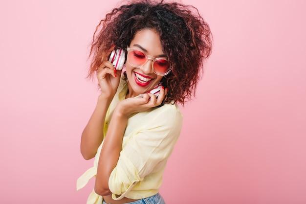 Verlegen zwarte vrouw met glanzende huid die lacht terwijl ze aan het chillen is met goede muziek. schattig mulat meisje met stijlvolle make-up ontspannen in koptelefoon. Gratis Foto