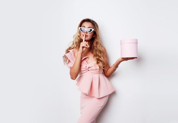 Verleidelijke blonde vrouw met geschenkdoos en poseren in roze jurk over witte muur. winkelen en vieren concept. modieuze zonnebril. Gratis Foto