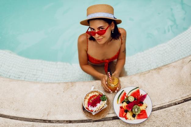 Verleidelijke donkerbruine tan vrouw in de rode zonnebril van kattenogen en strohoed het ontspannen in pool met plaat van exotisch fruit tijdens tropische vakantie. stijlvolle tatoeage. Gratis Foto