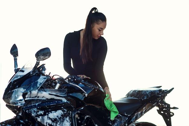 Verleidelijke jonge vrouw stijlvolle sport motorfiets wassen en veegt het van paars schuim. zorg dragen voor het voertuig. Premium Foto