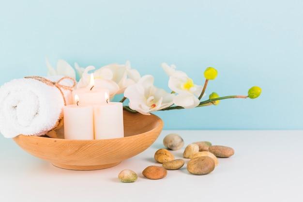 Verlichte kaarsen; handdoeken; bloem en spa stenen op witte ondergrond Gratis Foto