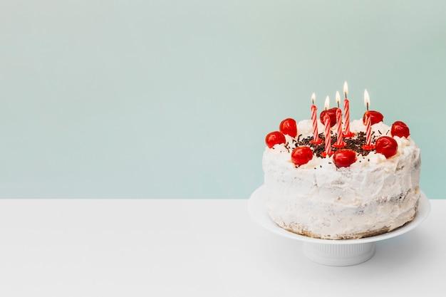 Verlichte kaarsen op verjaardagscake op caketribune tegen blauwe achtergrond Gratis Foto