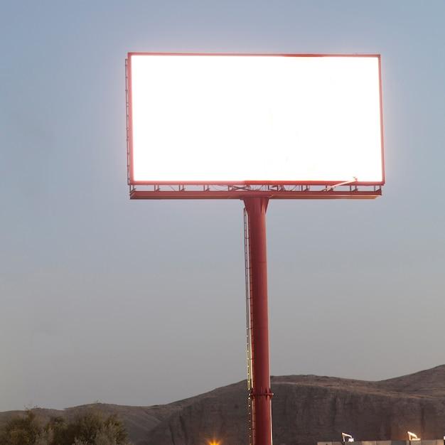 Verlichte leeg bord voor advertentie tegen blauwe hemel Gratis Foto