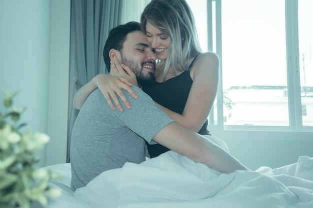 Verliefde paar kussen in bed. gelukkig paar liggen samen in bed. Premium Foto