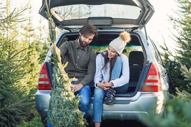 Verliefde paar laden vers gekapte kerstboom in een kofferbak van hun auto. jong gezin voorbereiden op vakantie. Premium Foto