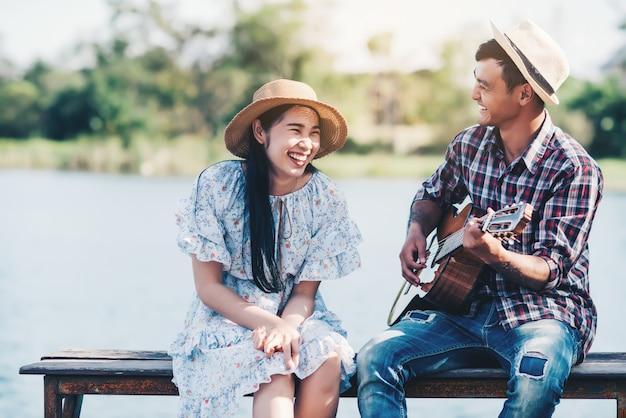 Verliefde paar met gitaarspelen bij rivier Gratis Foto