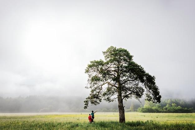 Verliefde paar ontmoet dageraad in het veld. mistige ochtend. de jongen en het meisje bij de boom. echtpaar reist. man en vrouw in het veld. eenzame boom. de man tilde het meisje op. liefhebbers reizen. volg mij Premium Foto
