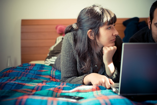 Verliefde paar op het bed met behulp van laptop Premium Foto