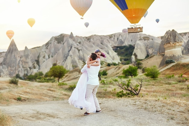 Verliefde paar staat op de achtergrond van ballonnen in cappadocië. man en vrouw op heuvel kijken naar een groot aantal vliegende ballonnen. turkije cappadocia fairytale landschap van bergen. bruiloft op de natuur Premium Foto