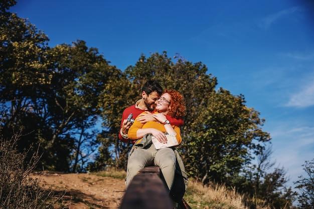 Verliefde paar vrije tijd doorbrengen in de natuur. paar zittend op een houten hek en knuffelen. Premium Foto