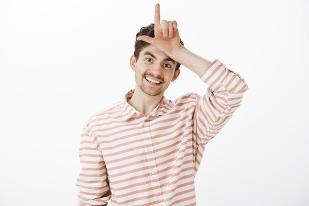 Verliezers blijven thuis. gelukkige vrolijke knappe europese man met snor en baard, l woord met hand over voorhoofd maken en breed glimlachen Gratis Foto