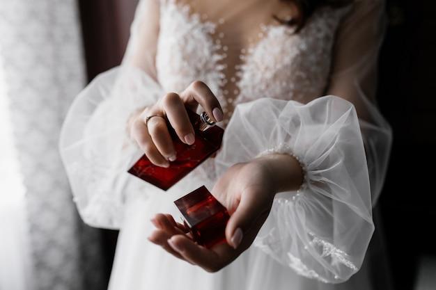 Verloofde in witte modieuze jurk met mooie mouwen en parfum in handen Gratis Foto