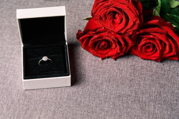 Verlovingsring en rode rozen als cadeau. concept van valentijnsdag en huwelijk. Premium Foto