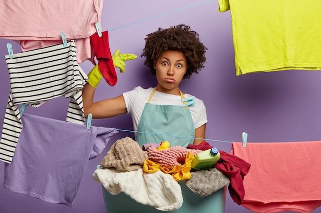 Vermoeide huisvrouw bezig met de was thuis Gratis Foto