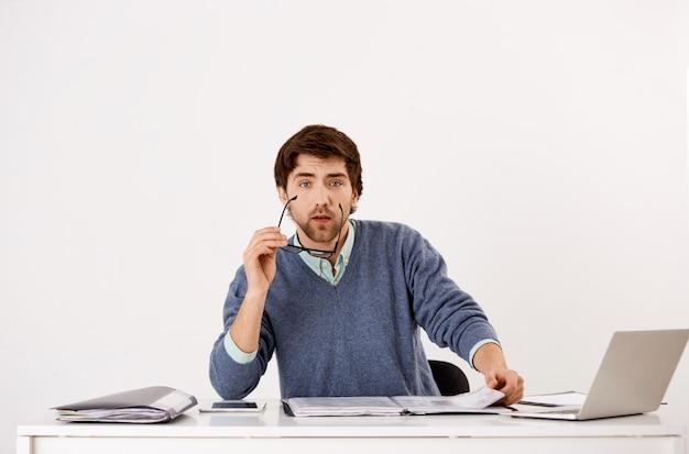 Vermoeide jonge bebaarde man, kantoormedewerker onderbroken van werk, leespot, startbril om te kijken, met behulp van laptop Gratis Foto