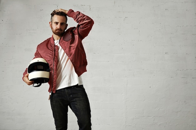 Vermoeide jonge motorrijder in rood bomberjack, zwarte spijkerbroek en wit t-shirt zijn kapsel aan te passen en zijn witte helm vast te houden Gratis Foto