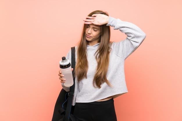 Vermoeide jonge sportvrouw over geïsoleerd roze met een fles water Premium Foto