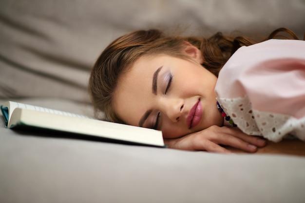 Vermoeide jonge vrouw die thuis een dutje doet, liggend op een bank met een boek Gratis Foto
