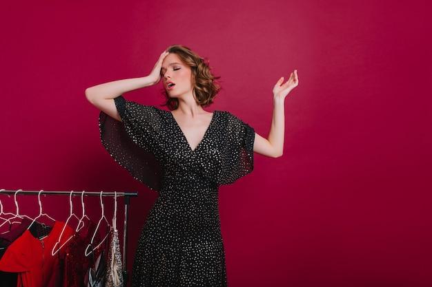 Vermoeide kortharige vrouw met gesloten ogen in de kleedkamer Gratis Foto