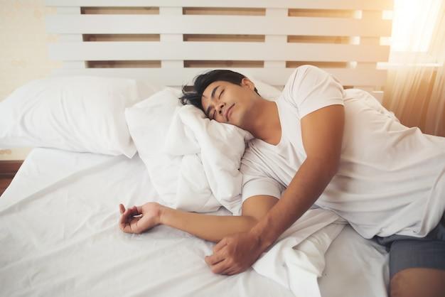 Vermoeide man die slaap aan bed ligt Gratis Foto