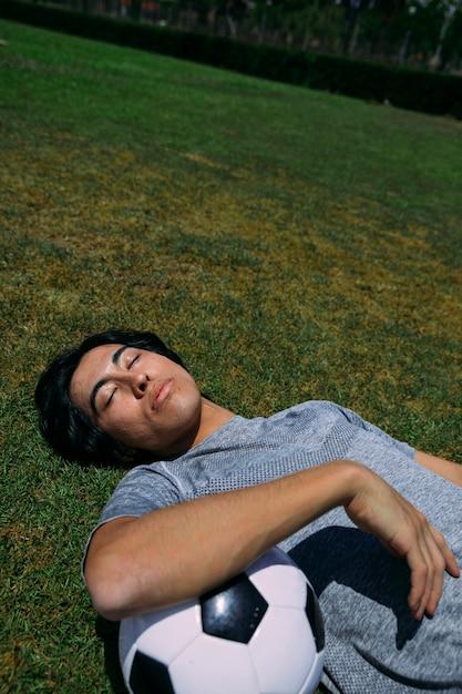 Vermoeide man met ogen gesloten op gras met voetbal liggen Gratis Foto