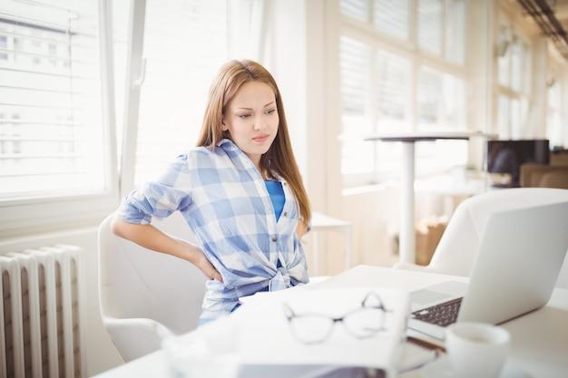 Vermoeide onderneemster die laptop op bureau in bureau bekijken Premium Foto