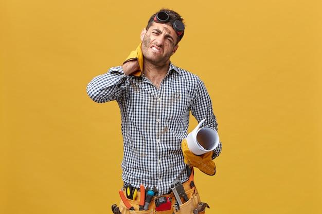 Vermoeide reparateur die uitgeput is, zorgt na een lange en stressvolle dag van het werk met zijn hand op de nek met pijn daar met handschoenen, riem met gereedschap en handschoenen en blauwdruk geïsoleerd Gratis Foto
