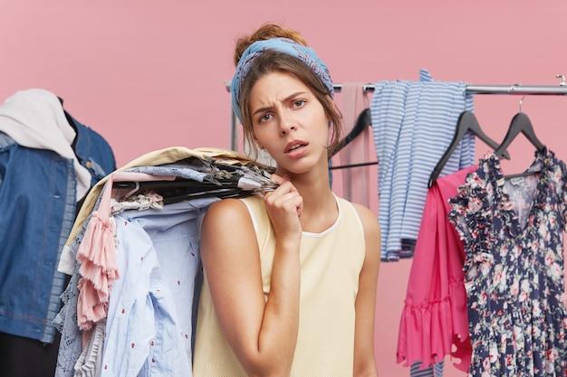 Vermoeide uitgeputte vrouw die boodschappen doet, stapel kleren op hangers houdt, de hele dag in boetieks en kledingwinkels doorbrengt terwijl ze probeert een outfit te kiezen voor een feestje. gepreoccupeerde vrouwelijke koper Gratis Foto