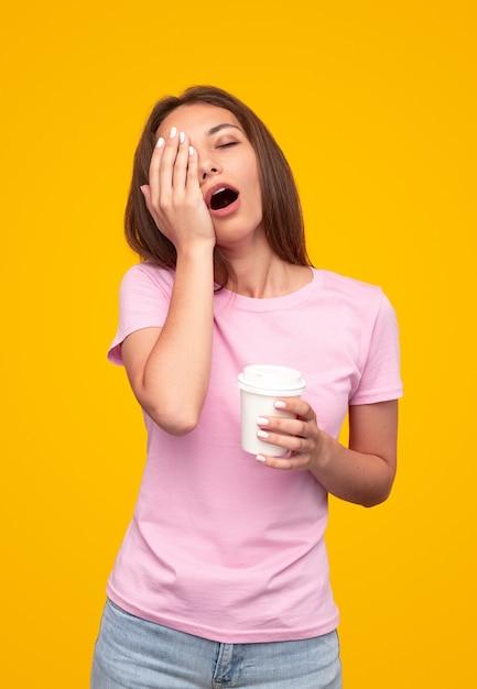 Vermoeide vrouw met kopje koffie om te gaan gapen en gezicht wrijven tegen gele achtergrond in de ochtend Premium Foto