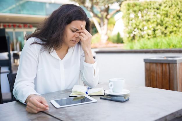 Vermoeide vrouw wat betreft neusbrug en zitting in straatkoffie Gratis Foto