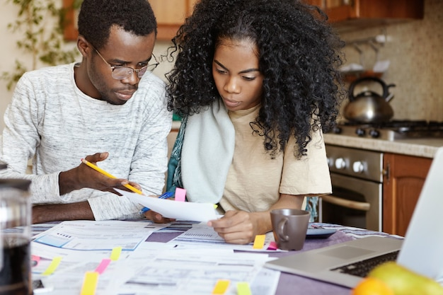 Verontwaardigde afrikaanse echtgenoot gebaart met potlood en verwijt zijn vrouw dat ze een fout heeft gemaakt bij het berekenen van rekeningen Gratis Foto