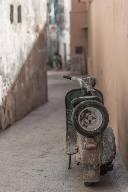 Verouderde indiase motor geparkeerd in smalle steeg. grungestijl, ontzet. Premium Foto