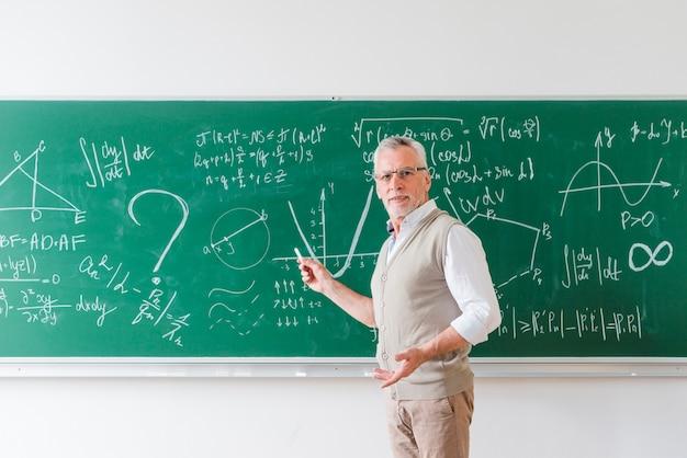 Verouderde wiskundeleraar die met krijt op bord richten Gratis Foto
