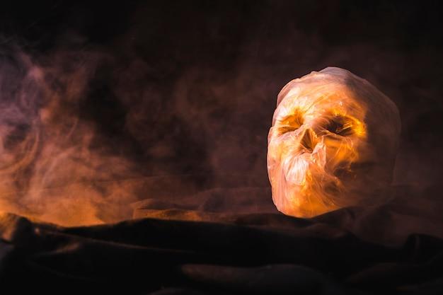 Verpakt in plastic zakschedel verlicht door oranje licht Gratis Foto