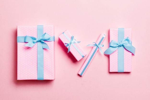 Verpakt kerst of ander vakantie handgemaakt cadeau in papier met blauw lint op roze achtergrond Premium Foto