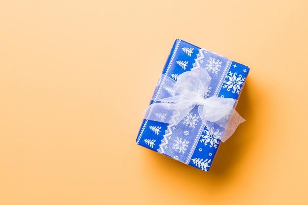 Verpakt kerstcadeau of andere handgemaakte kerstcadeau in papier met wit lint op oranje oppervlak. Premium Foto