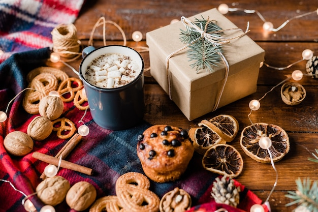 Verpakte geschenkdoos met conifeer en knoop bovenop omgeven door warme drank, kaneelstokjes, walnoten, schijfjes citroen en koekjes Premium Foto