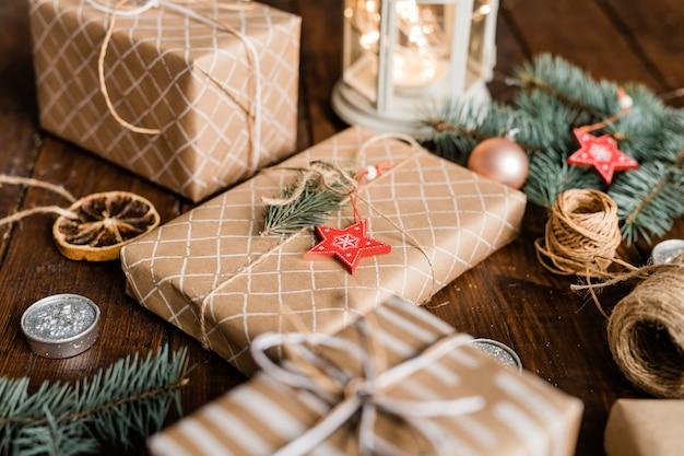 Verpakte geschenkdoos met conifeer en rode ster versiering aan de bovenkant omgeven door draden, kaars en andere dozen Premium Foto