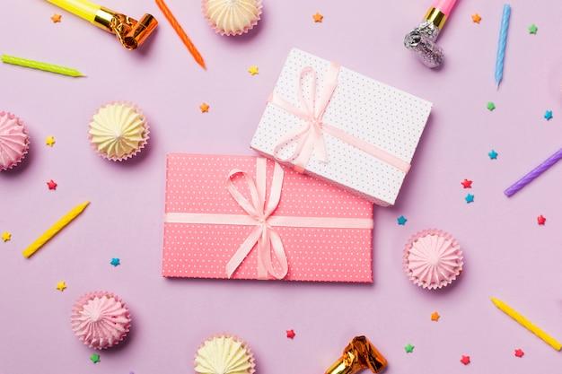 Verpakte geschenkdozen omringd met kaarsen; feest hoorn; hagelslag; geschenkdozen; aalaw op roze achtergrond Gratis Foto