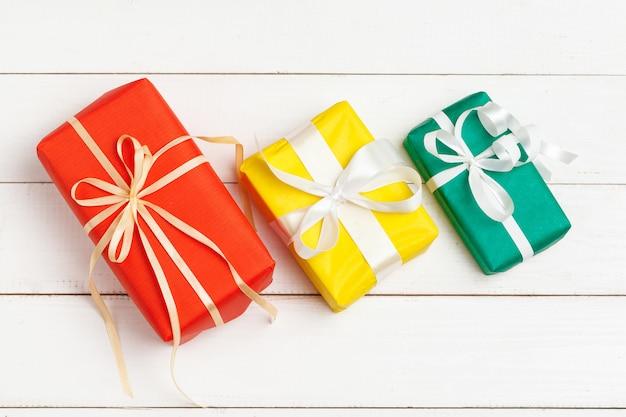 Verpakte geschenken met lint op witte houten bovenaanzicht als achtergrond Premium Foto